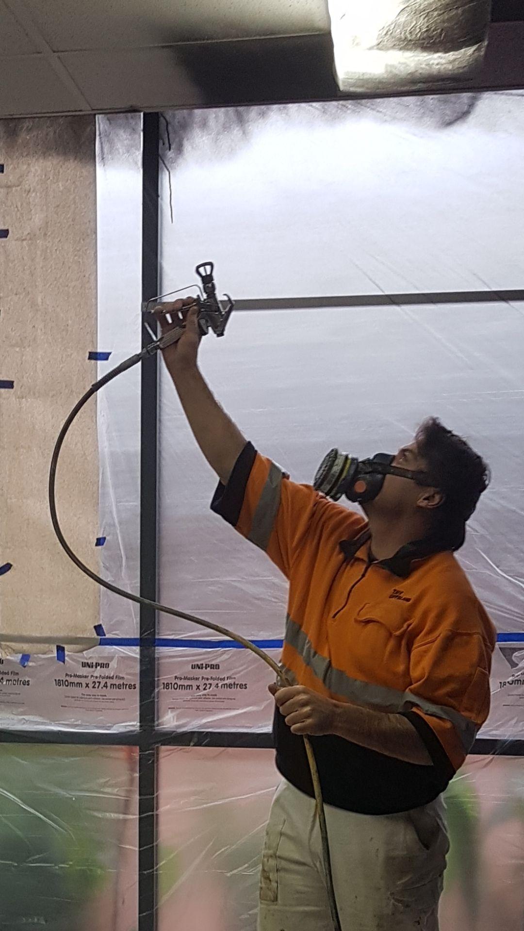 Teacher, Davin Nicholas, gets stuck into the painting