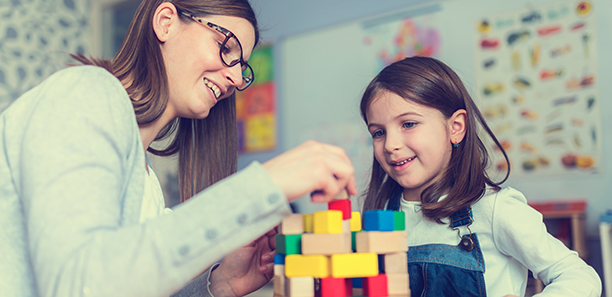 Young child plays with blocks as the teacher helps.