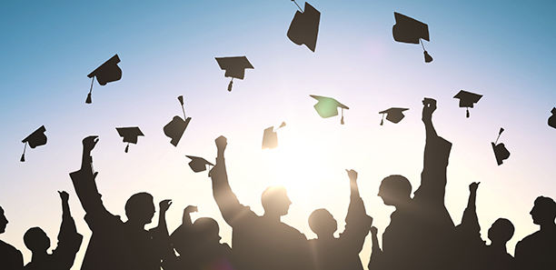 Graduates holding their caps in the air